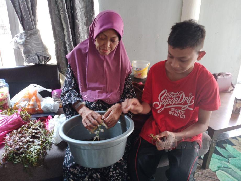 HAJIJAH Pawi sedang memotong sayur untuk di masak bersama anak lelakinya, Muhammad Zulirfan Zulkifli selepas keluar dari Hospital Port Dickson. FOTO MOHD KHIDIR ZAKARIA