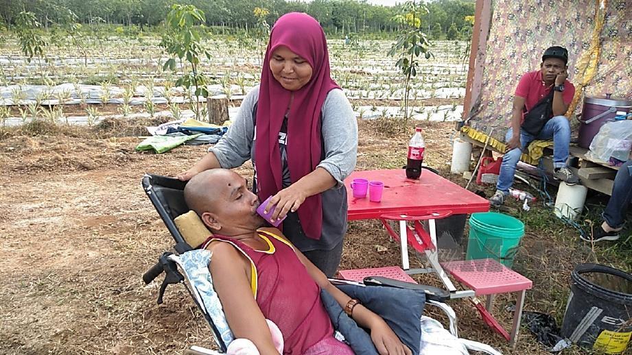 NOOR Aklima memberi air minuman kepada suaminya, Mohd Zuri. FOTO Siti Rohana Idris