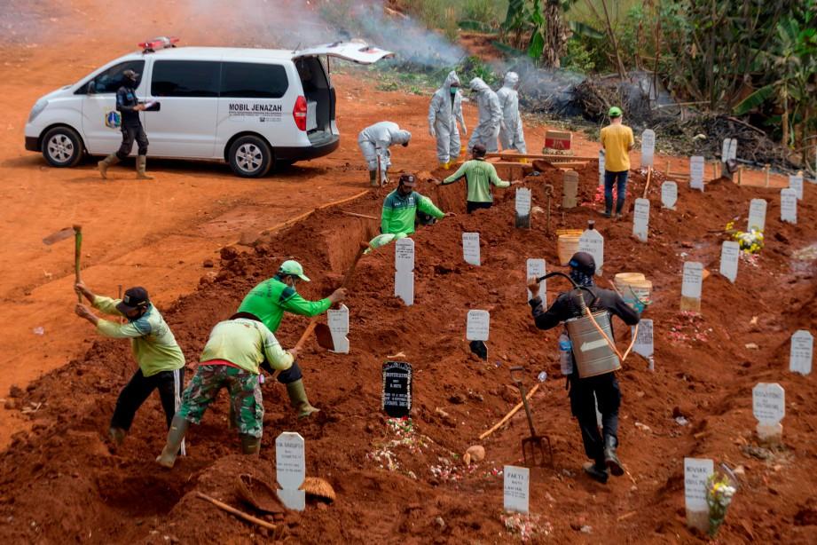 PEKERJA menggali kubur bagi pesakit Covid-19 di Jakarta. FOTO AFP
