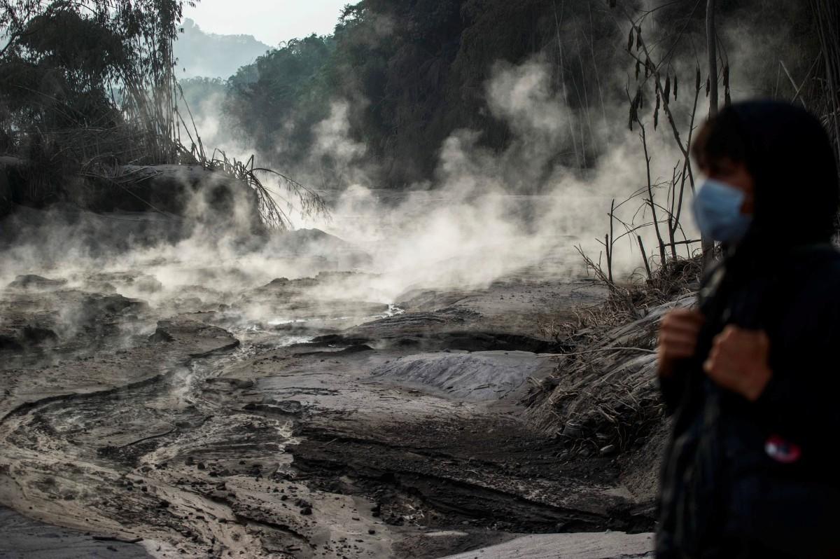 PENDUDUK melihat saliran yang terbentuk akibat lahar Gunung Berapi Semeru. FOTO AFP