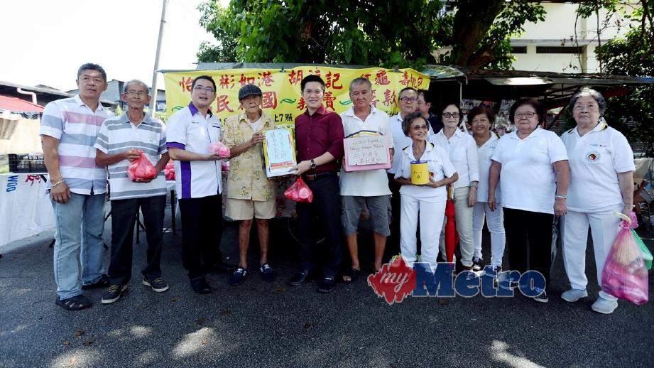 OH (empat kiri) menyerahkan duit kutipan dan sumbangan hasil jualan makanan oleh 25 peniaga dan pendudukdi Pasar Pasir Pinji kepada Wong (lapan kanan). FOTO Muhaizan Yahya