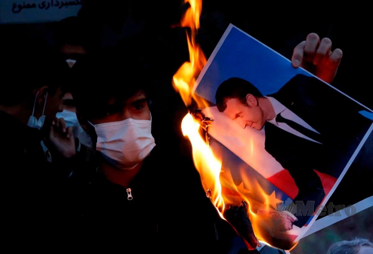 PENDUDUK Iran membakar gambar Presiden Perancis