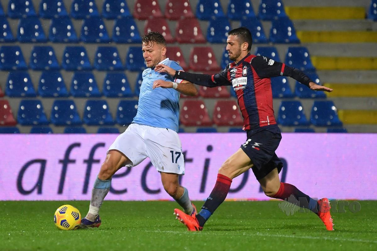 Penyerang Lazio, Ciro Immobile (kiri) melepasi kawalan pemain pertahanan Crotone, Giuseppe Cuomo pada aksi Serie A. FOTO Agensi