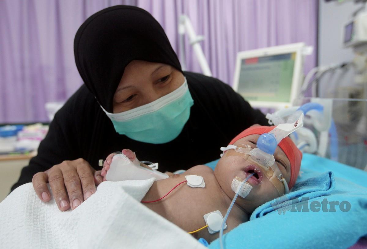 YASMI Mamu-U Ma, bersama Muhammad yang menghadapi jantung berlubang dan sindrom down. FOTO Amirudin Sahib.