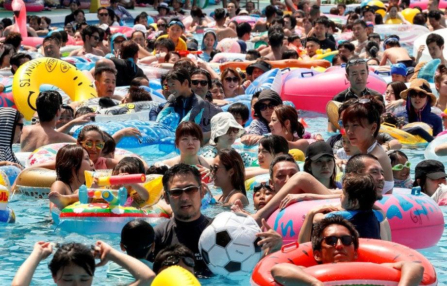 PENGUNJUNG mengambil kesempatan untuk mandi dengan lama di taman tema Toshimaen akibat cuaca terlalu panas. Foto/EPA