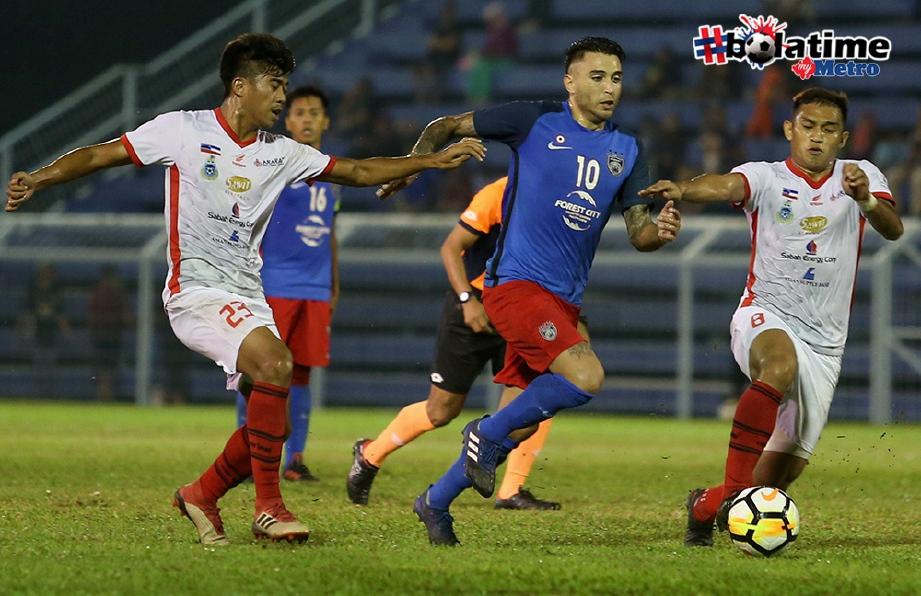 PEMAIN JDT II, Nicalos Alberto Fernandez (tengah) diasak pemain Sabah, Mohd Azzizan Nordin (kanan) di Stadium Majlis Perbandaran Pasir Gudang. FOTO/MOHD AZREN JAMALUDIN