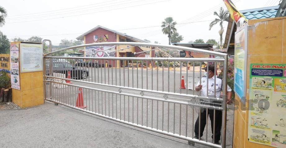 PENGAWAL keselamatan menutup pagar Sekolah Menengah Kebangsaan (SMK) Sungai Tapang di Kuching akibat jerebu. FOTO arkib NSTP