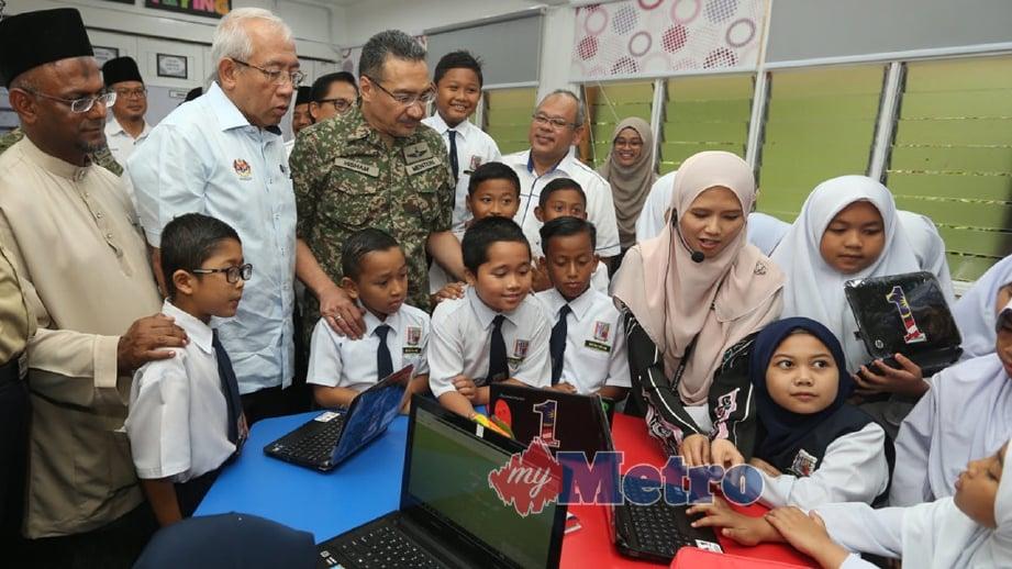 HISHAMMUDDIN (tengah) diiringi Salleh (kiri) dan Mahdzir (tiga kiri) beramah mesra bersama murid pada sesi lawatan ke kelas interaktif di Sekolah Kebangsaan Sultan Sir Ibrahim, Kem Batalion ke-5 RAMD, Kluang. FOTO Adi Safri