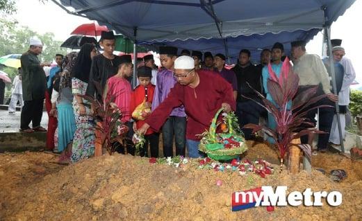 AHLI keluarga menabur bunga mawar di pusara Allahyarham Datuk Abdul Kadir Annuar, 82. FOTO Hairul Anuar Abd Rahim