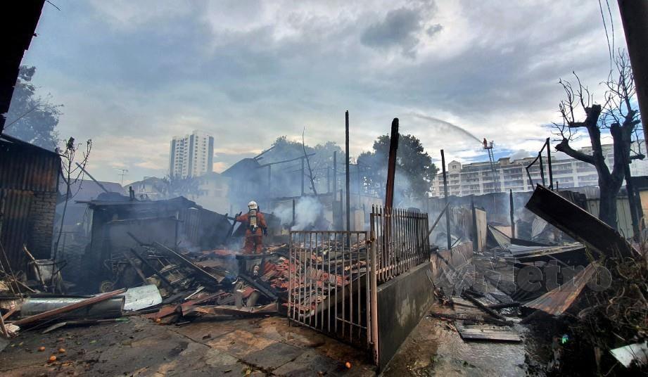 ANGGOTA berusaha memadamkan kebakaran yang memusnahkan lapan rumah kampung di Taman Cemerlang. FOTO Mikail Ong