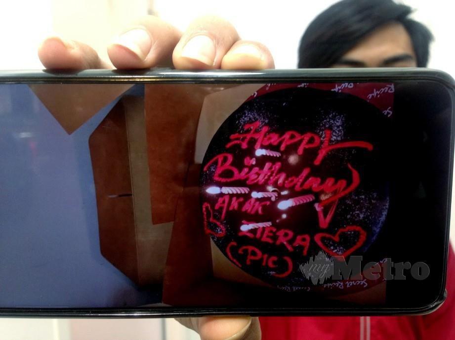 Rakan mangsa menunjukkan gambar kek yang ditempah untuk menyambut ulang tahun kelahiran mangsa di Melaka Raya hari ini. Foto Muhammad Zuhairi Zuber