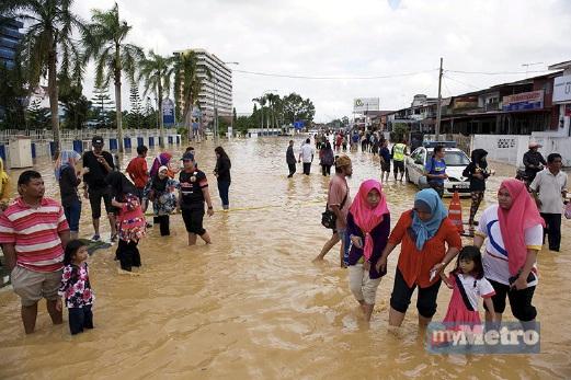 ORANG ramai mengharungi banjir di Bandar Kota Bharu. FOTO Bernama