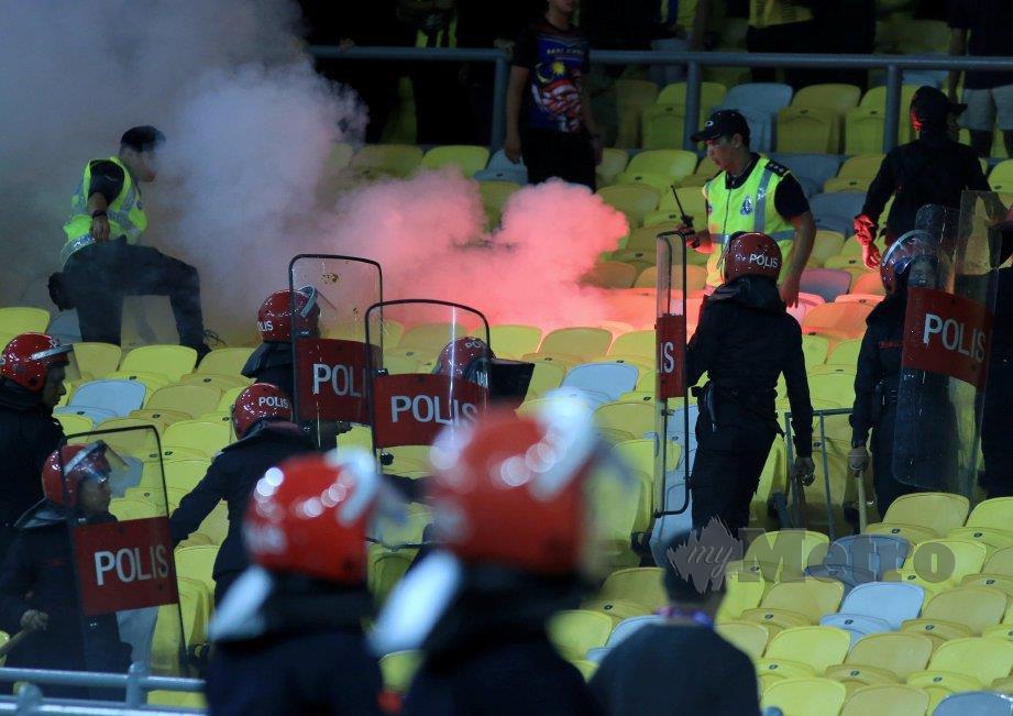 ANGGOTA polis memadamkan suar yang dibaling penyokong pasukan bola sepak Indonesia. FOTO Mohd Yusni Ariffin