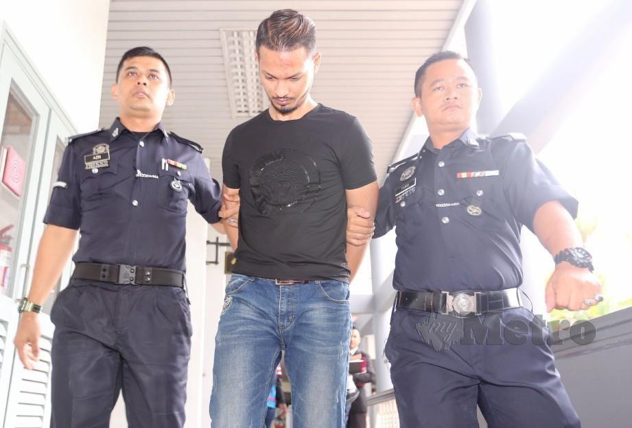 ZAHARI (tengah) diiringi polis keluar dari Mahkamah Majistret Ayer Keroh. FOTO Rasul Azli Samad