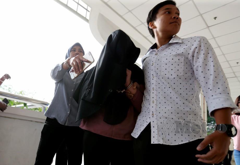 NORAINI (menutup muka) ketika dihadapkan ke Mahkamah Sesyen Seremban. FOTO Iqmal Haqim Rosman