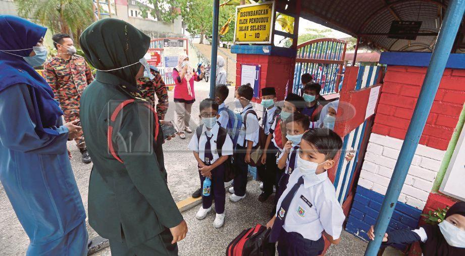 PASUKAN perubatan memberi bantuan kepada murid yang terhidu sisa toksik di SK Taman Pasir Putih, Pasir Gudang, semalam. FOTO Hairul Anuar Rahim.