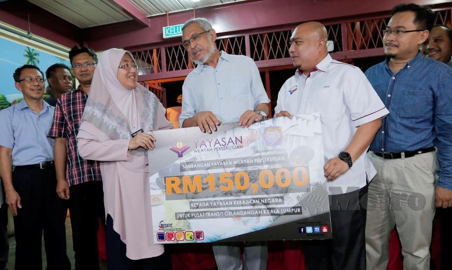 KHALID (tengah) menyaksikan penyerahan replika cek berjumlah RM150,000 daripada Zaizalnizam (dua dari kanan) kepada Che Asmah pada Majlis Penyerahan Sumbangan untuk Pusat Transit Gelandangan Kuala Lumpur, hari ini. FOTO Aizuddin Saad.