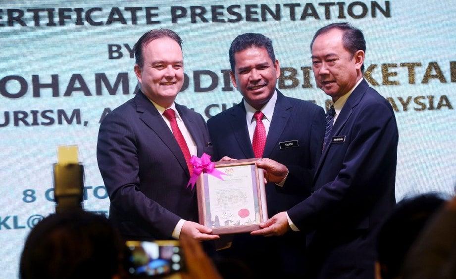ABDUL Khani (tengah) dan Pengerusi Tourism Malaysia, Datuk Ahmad Shah Hussein Tambakau (kanan) menyerahkan sijil operator pelancongan kepada Ketua Dasar Awam di Korporat Kumpulan TUI dan Perhubungan Dalaman, Frank Puttmann.