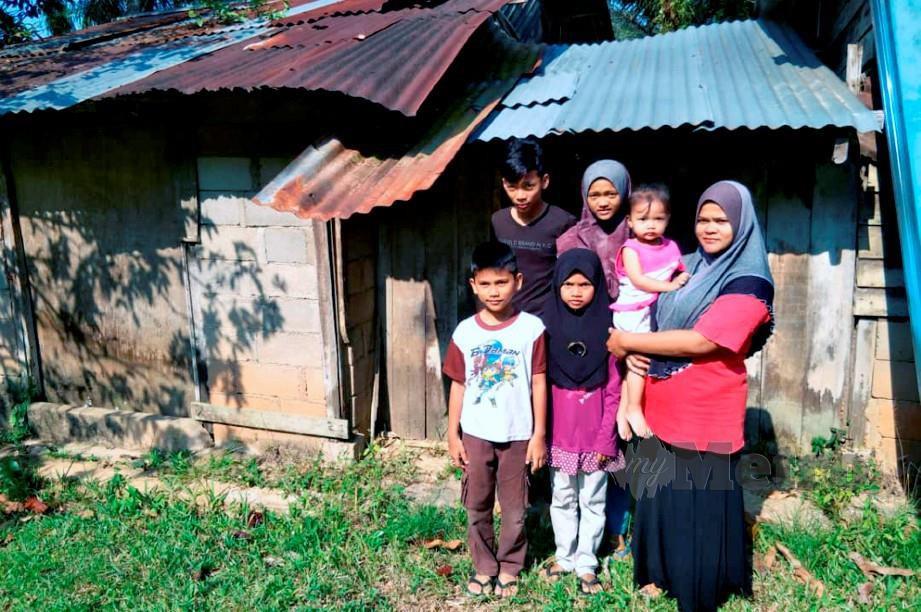 KHATIJAH Abdullah, 37 bersama lima anaknya bergambar kenangan di hadapan rumah usang yang menjadi tempat tinggal selama 15 tahun ketika ditemui di Kampung Anai, dekat Kampung Limau Kasturi. FOTO Ramli Ibrahim
