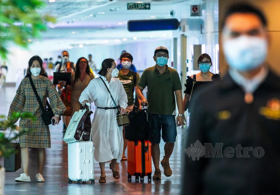 SEBAHAGIAN pelancong memakai penutup muka dan hidung berikutan penularan wabak 2019 Novel Koronavirus (2019-nCoV) di Terminal Lapangan Terbang Antarabangsa Kuala Lumpur 2 (KLIA2). FOTO Luqman Hakim Zubir