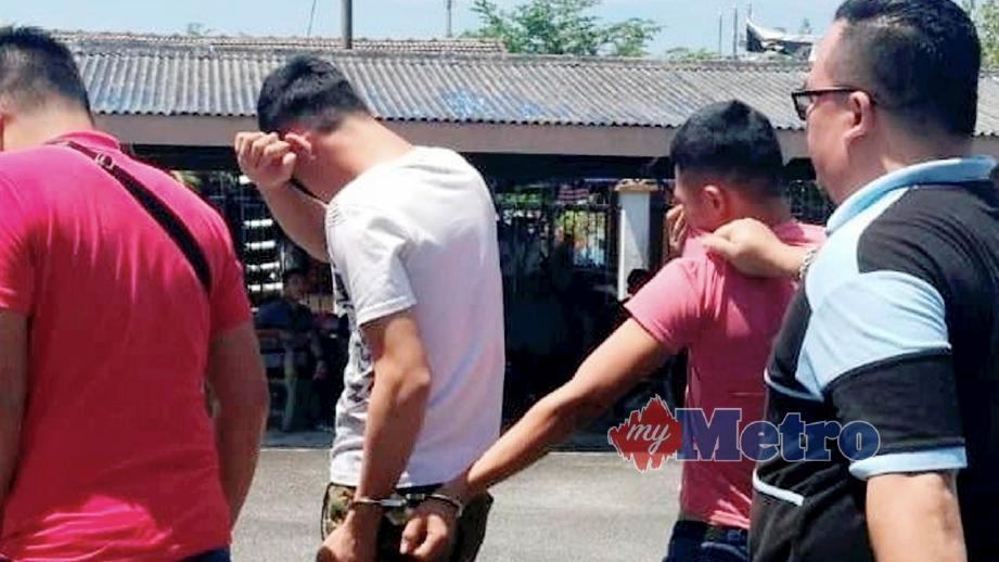 KEDUA-DUA suspek (tengah) yang menyamun kedai 24 jam dibawa anggota polis ke Mahkamah Majistret Dungun. FOTO Rosli Ilham