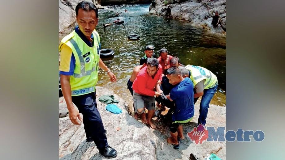 PENDUDUK kampung membantu anggota polis mengangkat dua sahabat yang lemas. FOTO Rosli Ilham