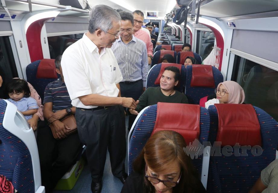 Kamarudin (kiri) dan Mohd Rani (dua kiri) beramah mesra dengan penumpang ETS yang pulang awal ke kampung halaman bagi menyambut hari raya Aidilfitri di Setesen KL Sentral. FOTO Owee Ah Chun