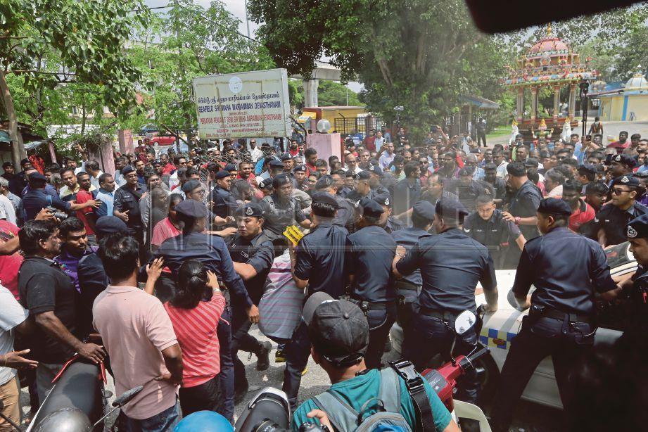 ANGGOTA polis bertindak mengawal kekecohan yang berlaku di kuil Sri Maha Mariamman, USJ 25, Subang Jaya, hari ini. Foto HAFIZ SOHAIMI
