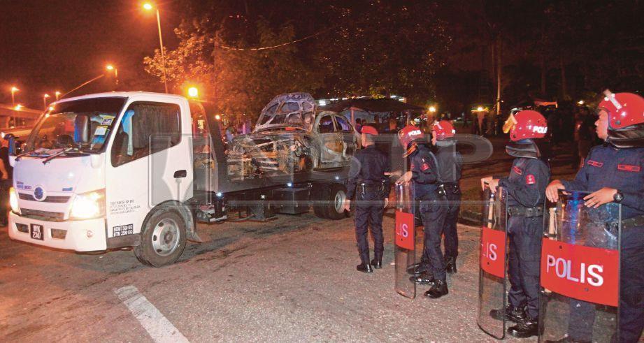 TRAK penunda membawa keluar kereta yang rosak dalam kejadian rusuhan di hadapan Kuil Sri Maha Mariamman, USJ 25, Subang Jaya, malam ini. Foto MAHZIR MAT ISA