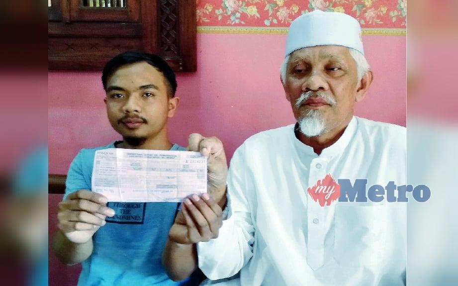 Md Yatim dan Muhammad Arash menunjukkan resit pembayaran majlis konvokesyen yang telah dibayar sebelum dimaklumkan pelajar terbabit dinyahsenaraikan dari senarai penerima. FOTO Abdel Hudzairee Mohd Yasak