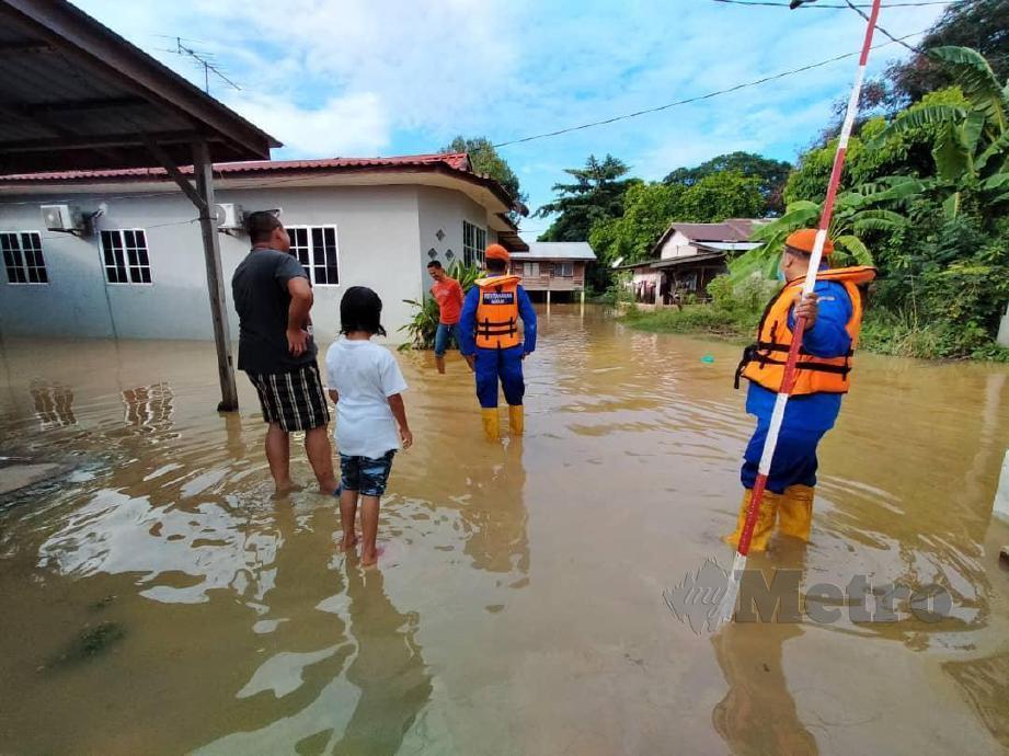 ANGGOTA APM Kubang Pasu melakukan pemantauan di kawasan Kampung Nang Mah yang dinaiki air sedalam 0.3 hingga 0.5 meter dalam kejadian banjir kilat. FOTO IHSAN APM