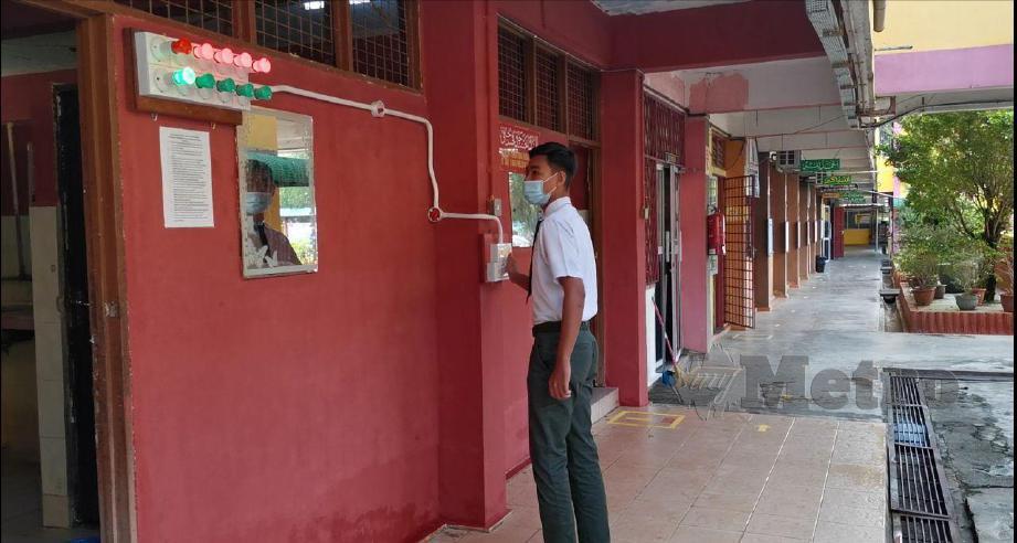 PELAJAR memetik suis lampu sebelum masuk ke dalam tandas dan selepas keluar tandas yang menjadi peraturan baharu di SMK Syed Abu Bakar. FOTO NOR FARHANI CHE AD