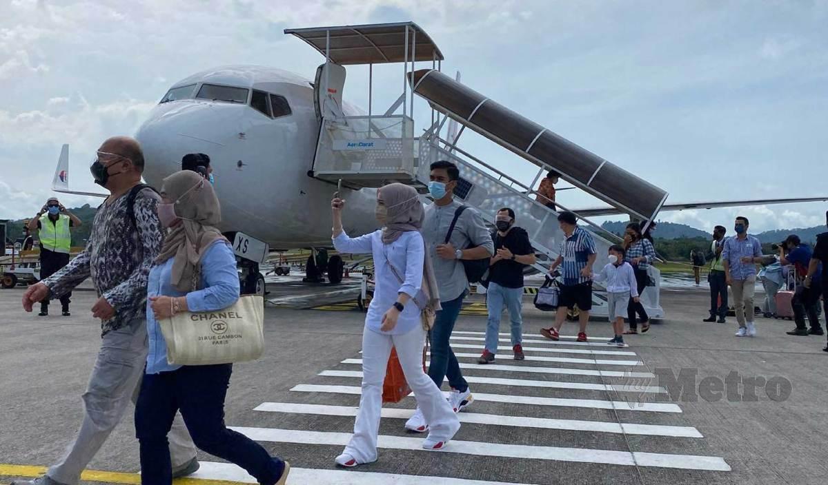 KUMPULAN pertama pelancong domestik yang menaiki penerbangan dari Lapangan Terbang Antarabangsa Kuala Lumpur (KLIA) ke Lapangan Terbang Antarabangsa Langkawi (LTAL) hari ini. FOTO M Hifzuddin Ikhsan