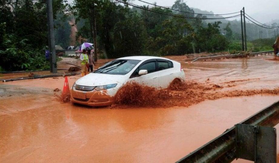 KENDERAAN  meredah banjir lumpur di  Jalan Gua Musang-Lojing.