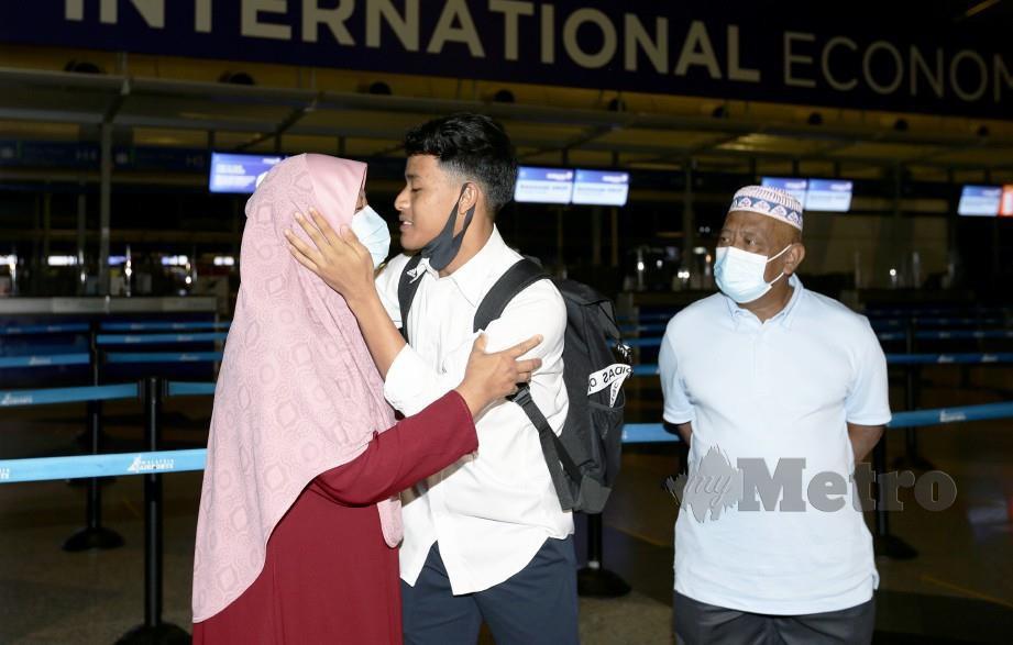 LUQMAN (tengah) mencium ibunya, Hasmah sebelum  berlepas ke Eropah untuk mewakili kelab utama di Belgium, KV Kortrijk di Lapangan Terbang Antarabangsa Kuala Lumpur (KLIA). Turut kelihatan bapanya, Shamsudin Mahmood. FOTO Mohd Fadli Hamzah