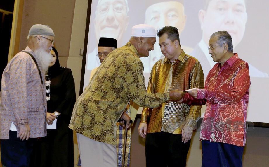 DR Mahathir Mohamad menyampaikan sumbangan kepada pesara yang mengidap penyakit kronik pada majlis makan malam Reunion Ex KBTC 2019. FOTO AHMAD IRHAM MOHD NOOR.