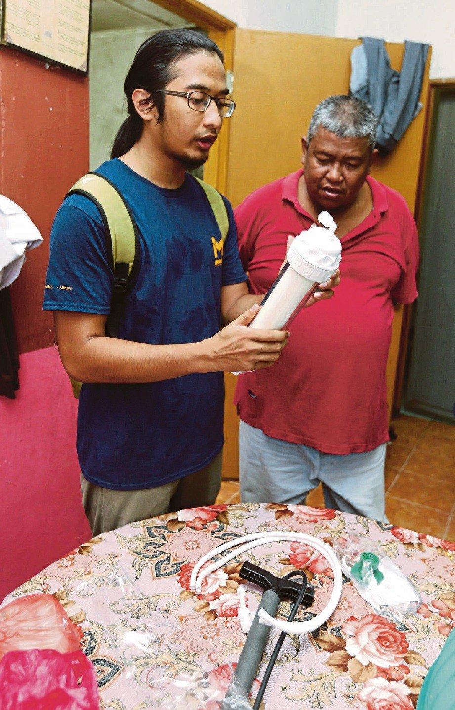NAQIUDIN membantu memasang penapis air di rumah keluarga Latif. FOTO Zunnur Al Shafiq