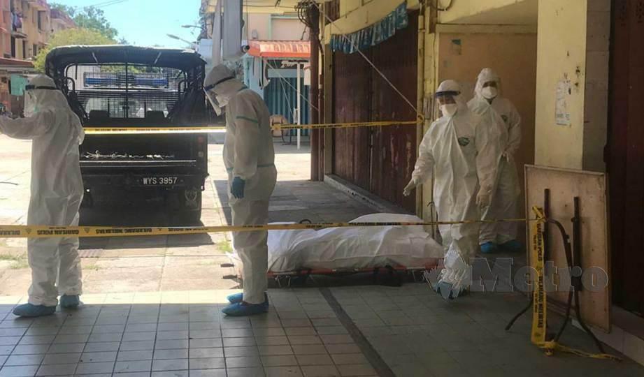 POLIS bersama kakitangan KKM lengkap berpakaian PPE mengangkat mayat warga India yang ditemui terbaring di bilik sewanya di Mangatal, Kota Kinabalu. FOTO Juwan Riduan