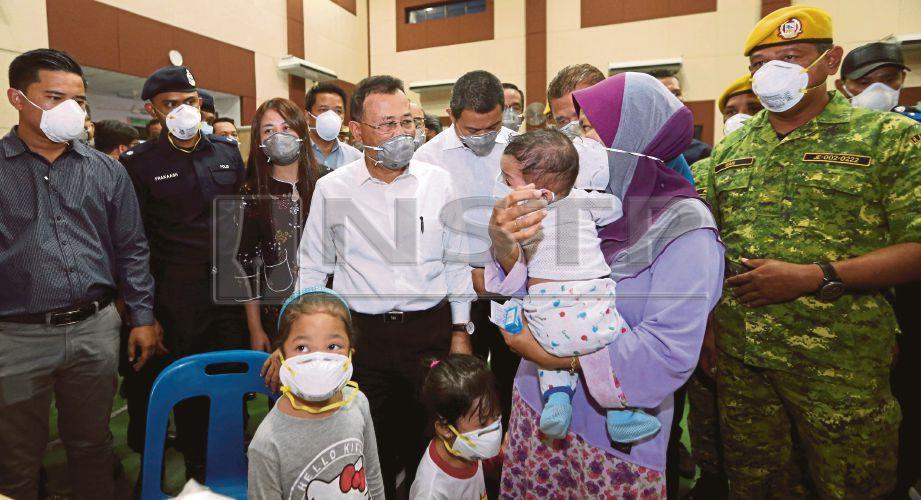 OSMAN (tengah) melawat mangsa yang mendapatkan rawatan kecemasan dipercayai terhidu gas kimia berbahaya di Dewan Komuniti Taman Pasir Putih, Pasir Gudang. FOTO Mohd Azren Jamaludin.
