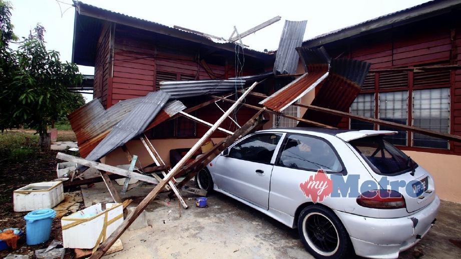 BUMBUNG rumah runtuh dan menimpa kereta akibat ribut di Kampung Tedong. FOTO Muhammad Zuhairi Zuber