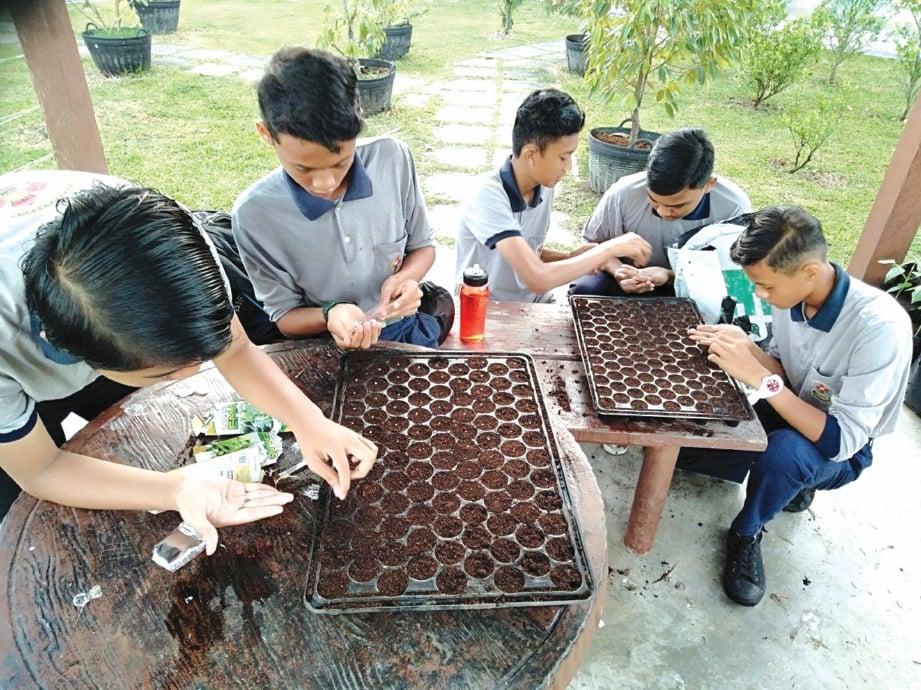 PROSES meletakkan benih turut dilakukan pelajar.