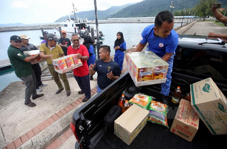 Anggota APM mengangkat barangan makanan untuk bekalan penduduk di Pulau Tioman di musim Monsun Timur Laut di Rompin hari ini. Foto Muhd Asyraf Sawal