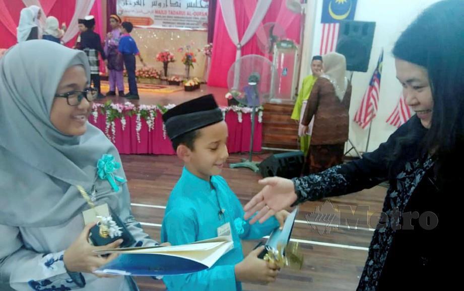 JUARA pertandingan mendeklamasi sajak Bahasa Mandarin, Nayli Nur Aisyah Muhamad Adam, 12, dan Hamzah Hassan, 10, menunjukkan piala yang diperoleh mereka kepada guru yang melatih, Tai Bee Yin (kanan) dalam Majlis Tadarus Al Quran bagi Sekolah Jenis Kebangsaan Cina (MTQSJKC), Sekolah-Sekolah Kementerian Pendidikan Malaysia (KPM) peringkat Negeri Kelantan 2019 yang diadakan di Sekolah Kebangsaan (SK) Sri Rantau Panjang 2. FOTO Syaherah Mustafa