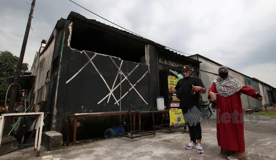 NURUL Ain bersama anaknya menunjukkan kedai mereka yang rosak selepas MBSA merobohkan beberapa struktur dengan diberi notis 24 jam di Bandar Baru Sungai Buloh. FOTO Eizairi Shamsudin