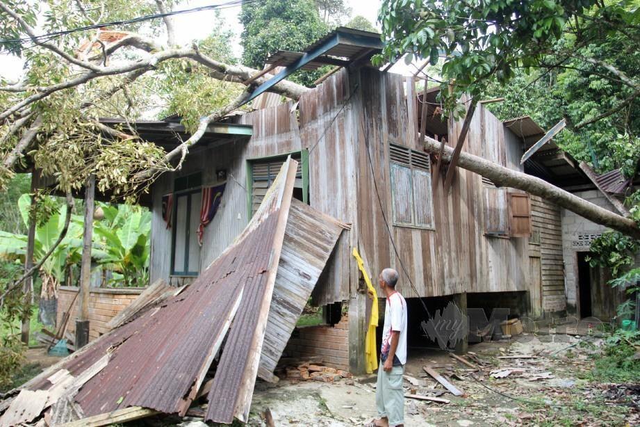 NOR Azman melihat keadaan rumahnya yang dihempap pokok durian. FOTO Nik Abdullah Nik Omar.