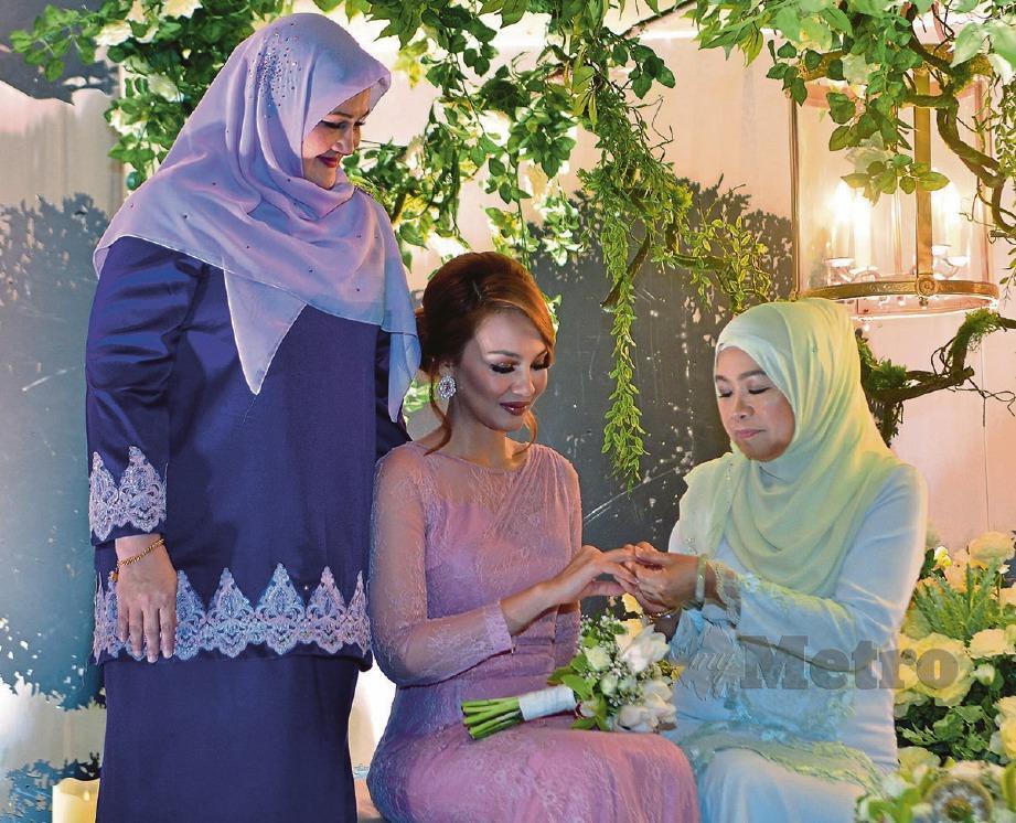 IBU Mu'izz, Nona Suin (kanan) menyarungkan cincin kepada Nadia (tengah) sambil diperhatikan ibu Nadia, Husmarita Hussain (kiri). -Foto FAIZ ANUAR