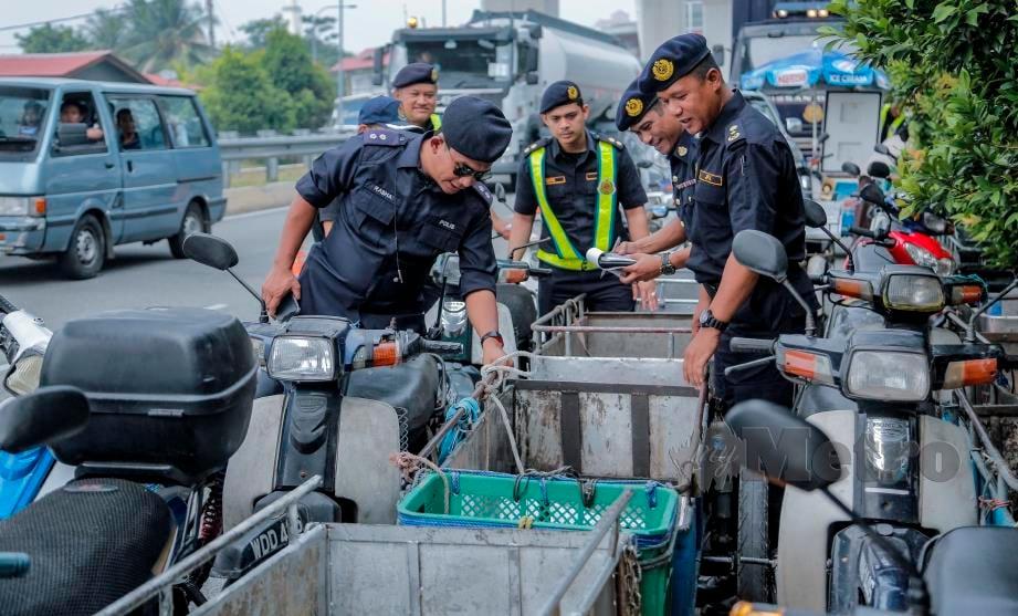 NAZLI (kanan) bersama pegawai JPJ dan polis memeriksa motosikal roda tiga tidak mengikut spesifikasi JPJ ketika operasi di Puchong Perdana, hari ini. FOTO Aizuddin Saad.