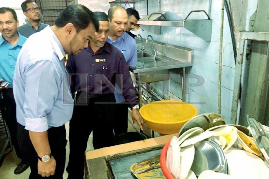 ANGGOTA Penguat kuasa Majlis Perbandaran Kuantan (MPK) memeriksa kawasan dapur restoran 24 jam yang tidak diuruskan dengan bersih dalam operasi di sekitar Kuantan. FOTO Ihsan MPK