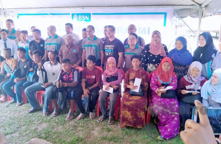 SERAMAI 12 remaja Orang Asli yang memeluk agama Islam di Kampung Lambok bergambar kenangan bersama rombongan Bank Simpanan Nasional (BSN) di Kampung Lambok. FOTO Ramli Ibrahim