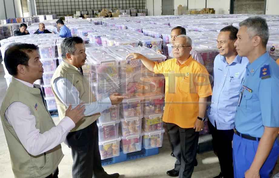 ISHAK (tiga dari kanan) bersama Zakaria (dua dari kiri) meninjau stok bekalan kit makanan NADMA untuk mangsa bencana ketika mengadakan lawatan kerja di Pusat Edaran FAMA, Pelabuhan Klang, hari ini. FOTO Faiz Anuar.